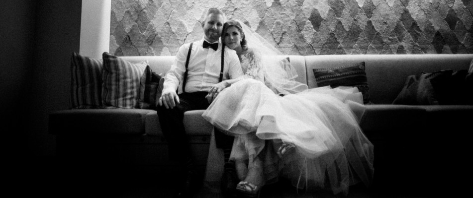Black and white photo of bride and groom posing for picture