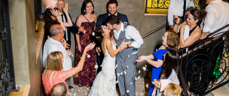 Bride and groom kissing on staircase surrounded by guests
