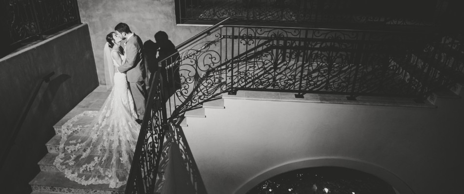 Black and white photo of bride and groom kissing on staircase